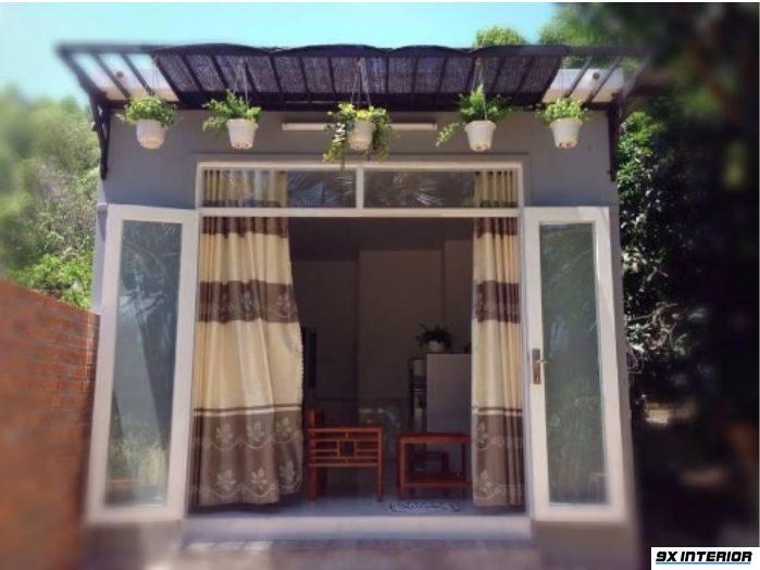 Nhà dùng cửa nhôm kính, phía trước trang trí đơn giản với các giỏ cây tươi